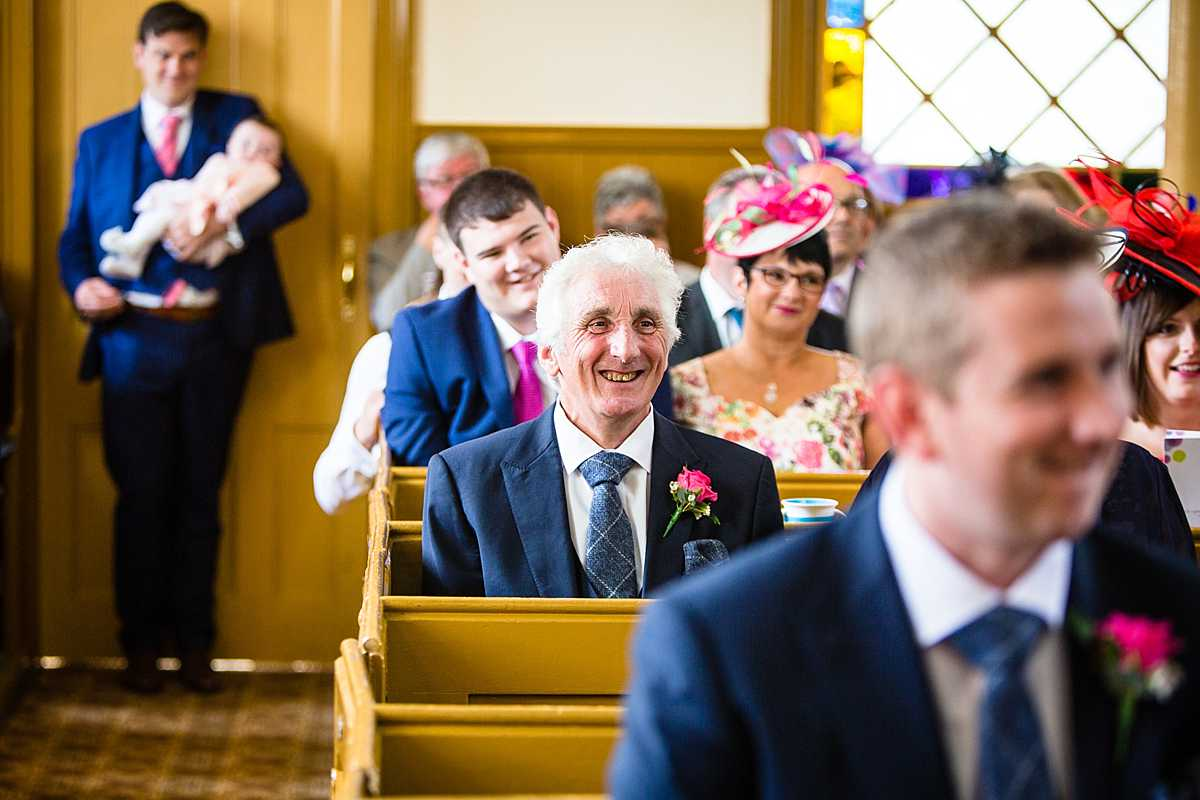 father of the groom with the biggest smile on his face as the church ceremony commences