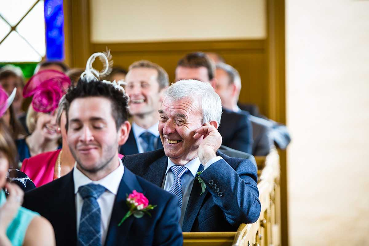 guests laughining holding his ear during ceremony in welsh wedding