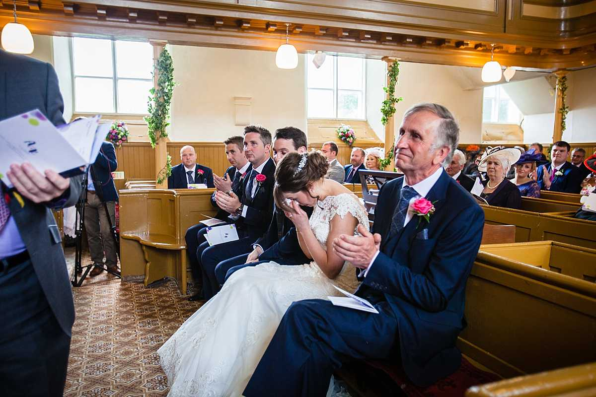 emotional bride wiping tears as bridesmaid does her reading