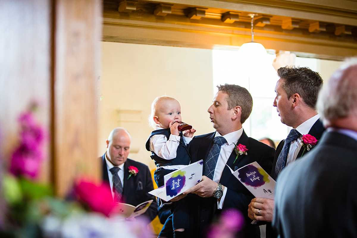 little boy jokingly drinking from dads hip flask in church wedding in Machynlleth