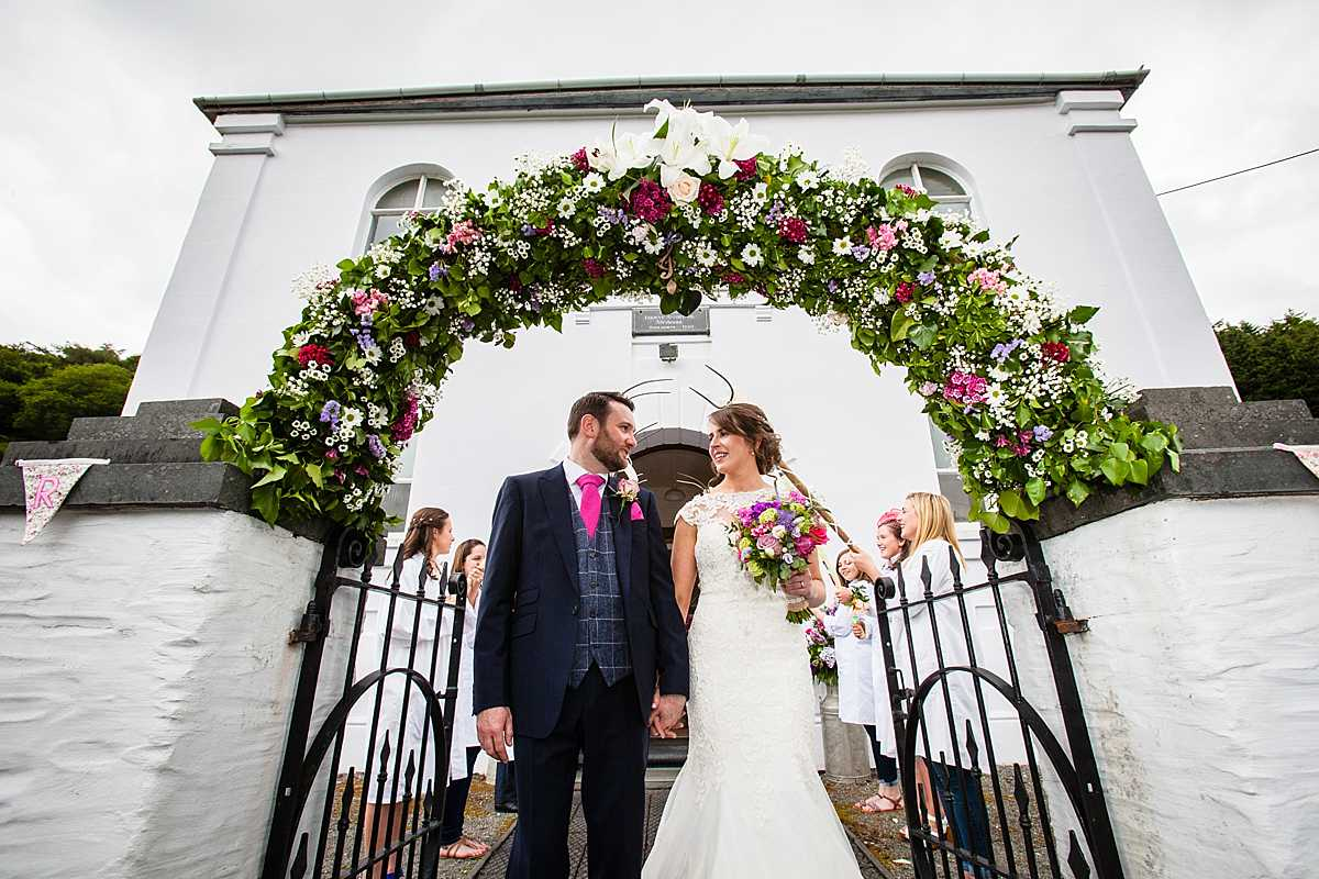 bride and groom looking at one another happily as they walk through the flower arch outside church