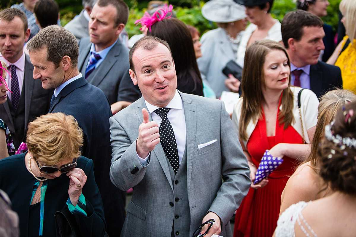 thumbs up from one of the male guests looking at the happy couple amongst the crowd