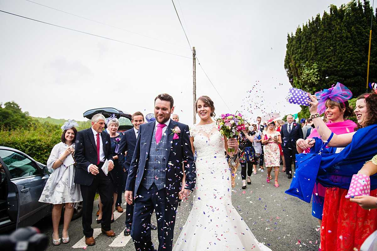 confetti shot as the bride and groom walk through the guests