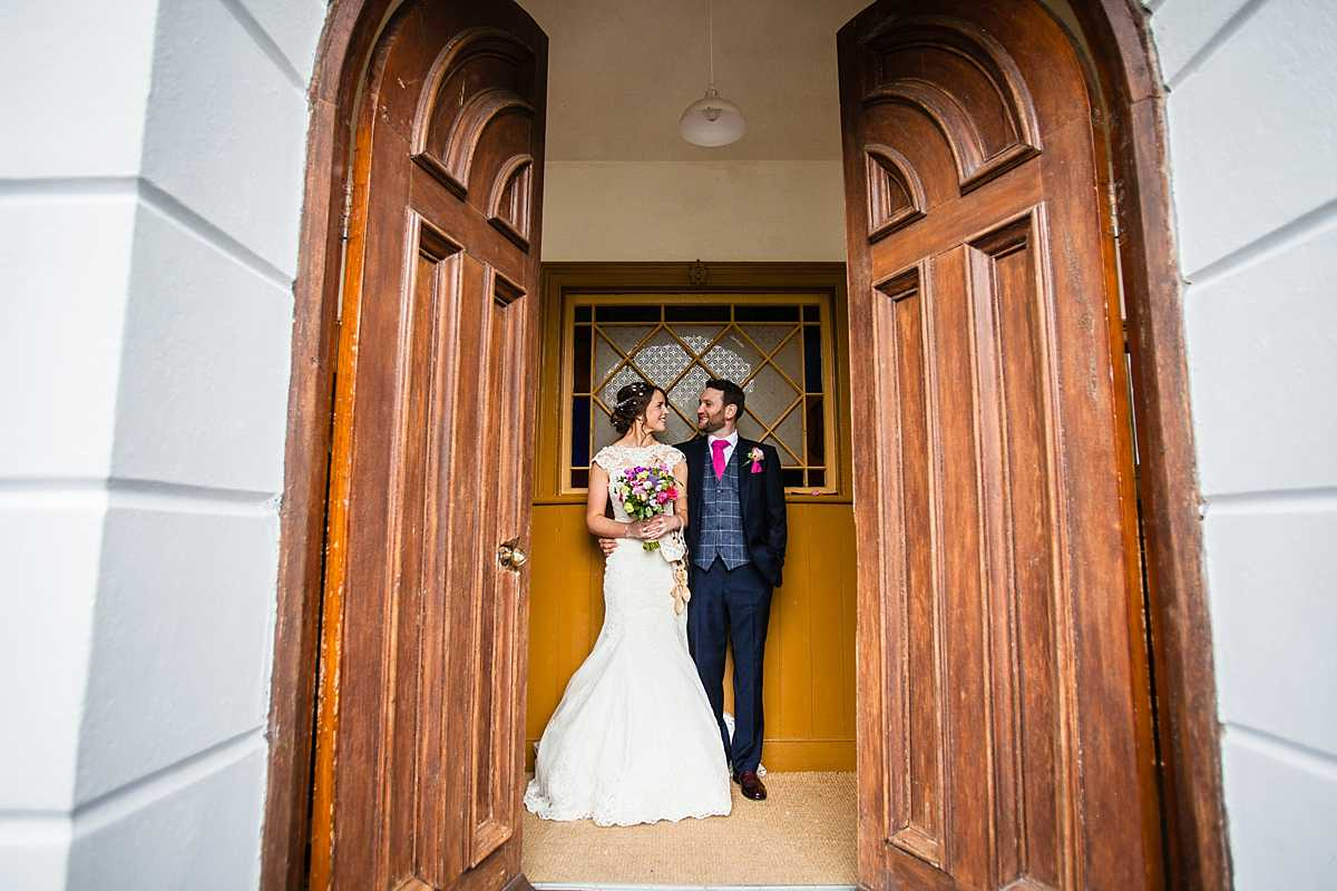 bride and groom looking at each other adoringly as they stand together in the gap between the chapel doors