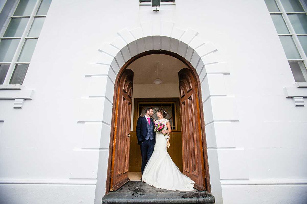 bride and groom framed in a beautiful chapel door way at wedding in Machynlleth