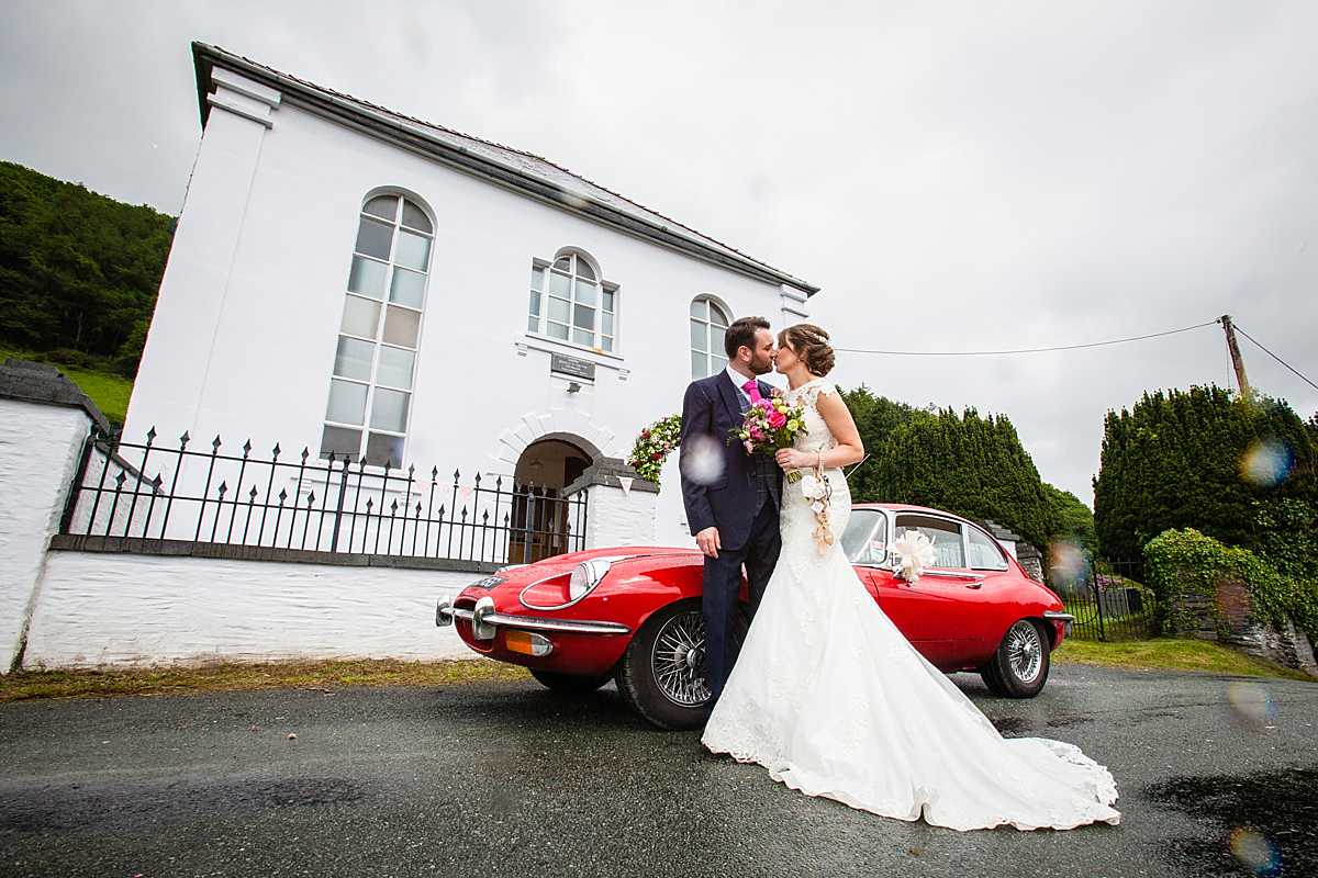 lovely photo of the bride and groom kissing with the whole of aberhosan chapel and red e-type jaguar in the background