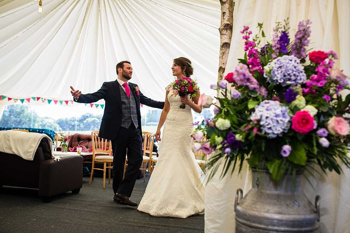 groom joking around with the bride as they wait to be announced in to the wedding breakfast in marquee in Machynlleth