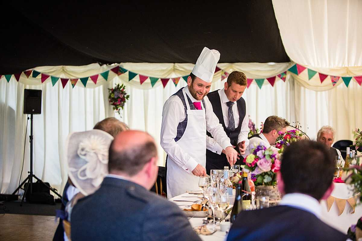 groom cutting the roast beef for main meal at marquee wedding in wales