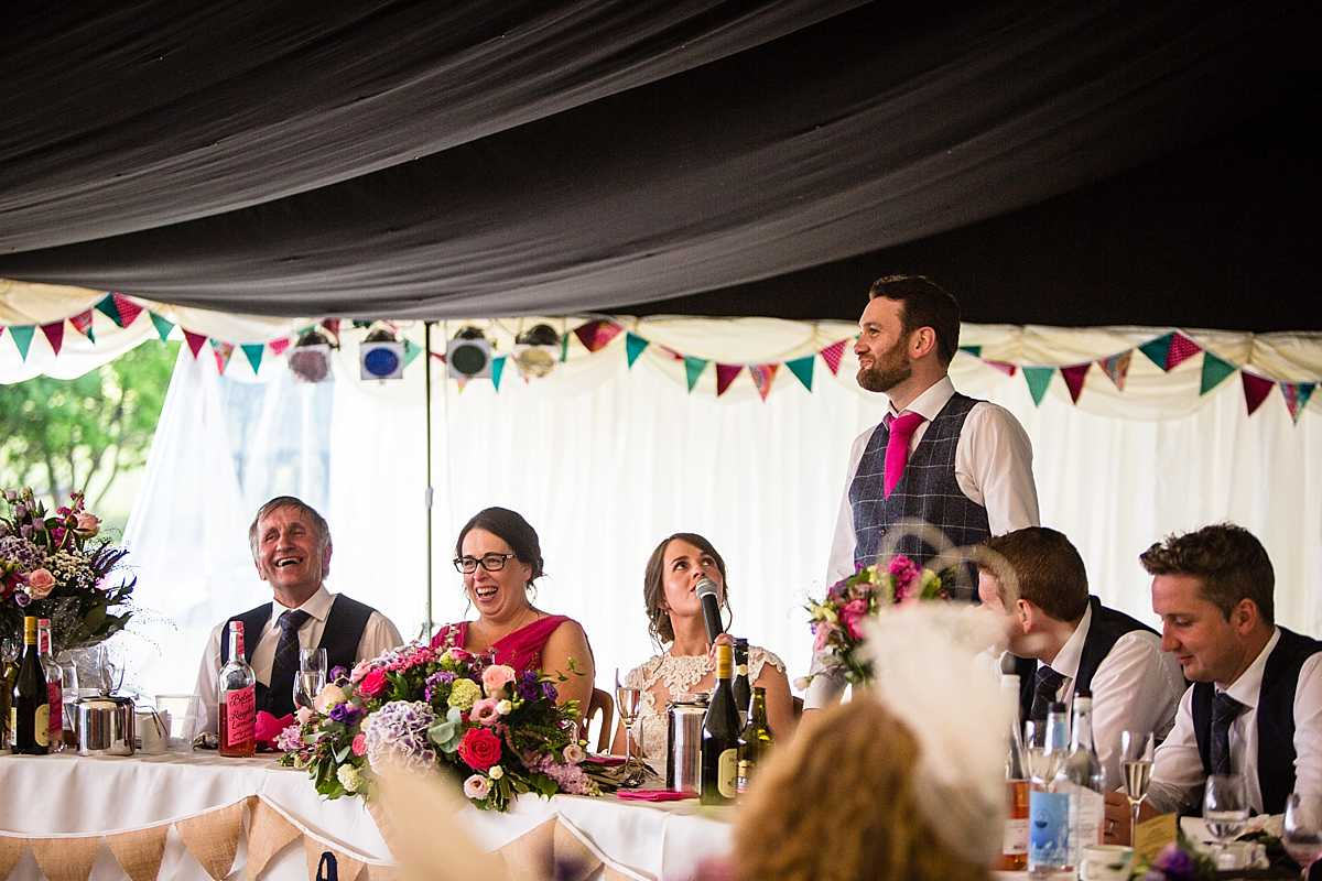 guests laughing out loud as the bride grabs the mic and corrects the groom in his speech to the guests