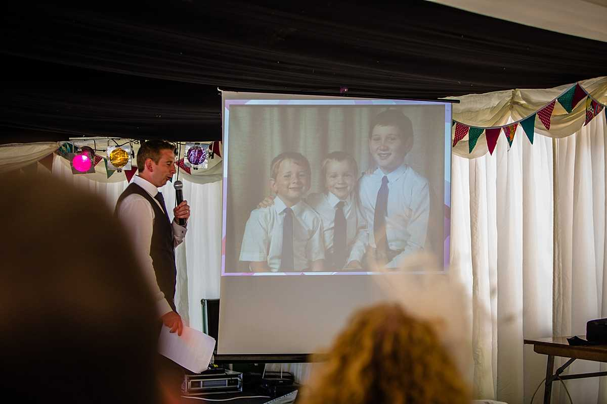 family photo on the projector as the two brothers do their speech about the groom who their is their brother