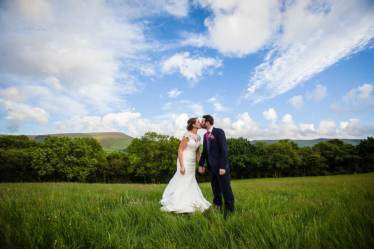 bride and groom standing the family home field leaning in for a kiss with beautiful fields and blue sky