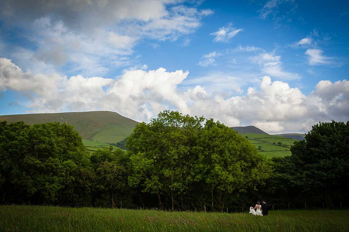 bride and groom walking further into the field with picturesque views in the background