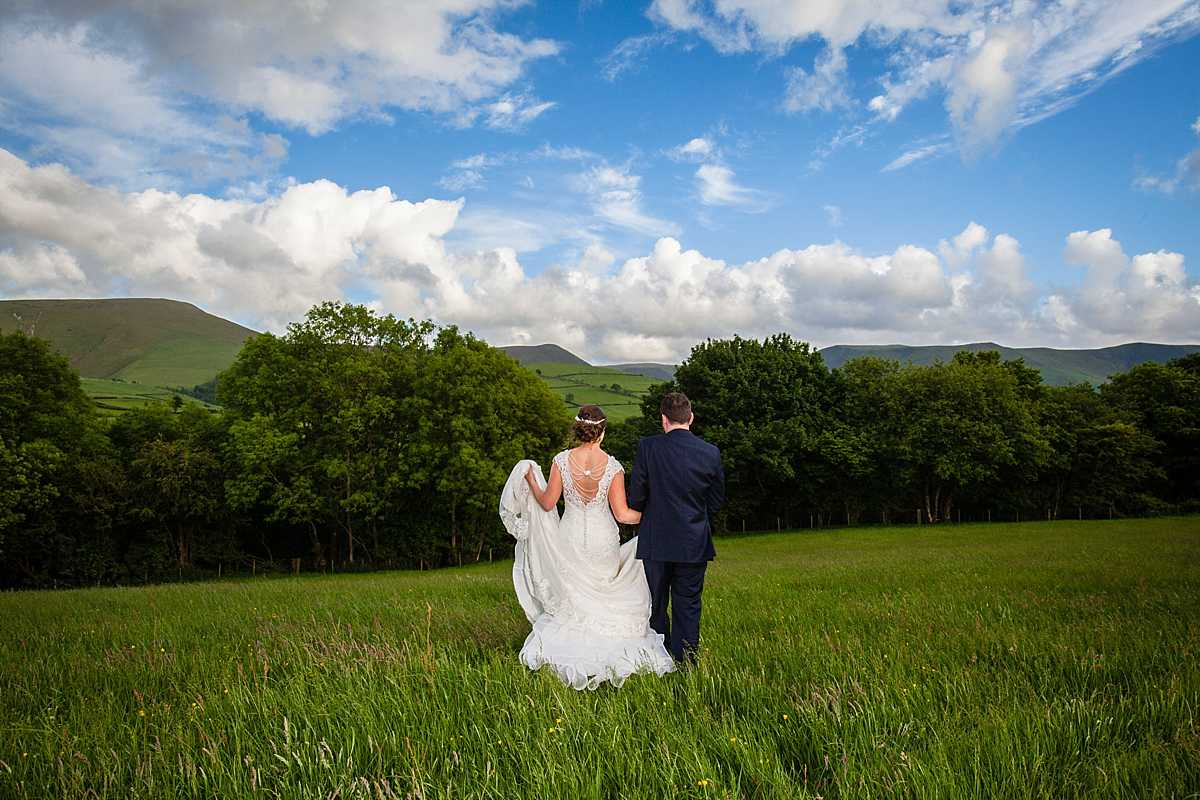 bride holding her dress up as she walks holding hands with her groom and beautiful views in the background
