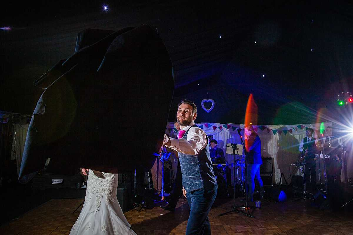 groom throwing his jacket as he is about to do the first dance at marquee wedding in Machynlleth