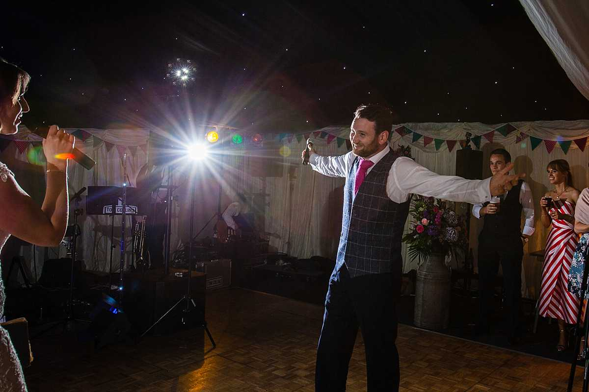 groom with his arms stretched out as he looks adoringly at his wife as she sings to him