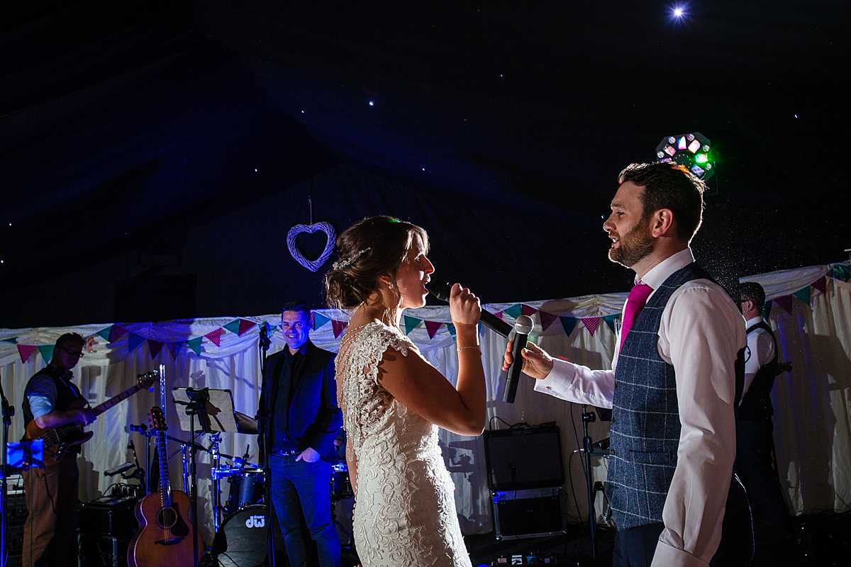 beautiful side lighting as the bride sings to the groom with the band in the background