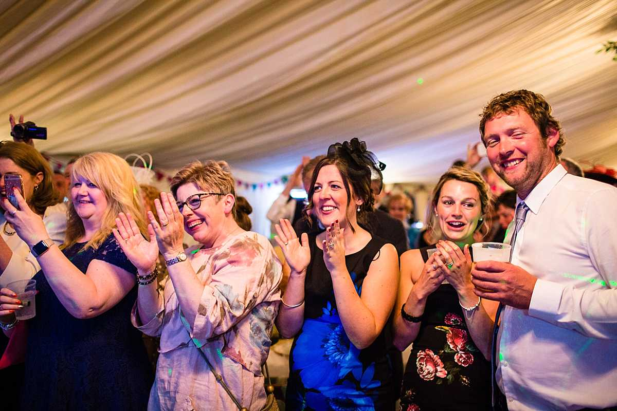 big applause to the bride and groom from their guests all standing and watching them do their first dance and song