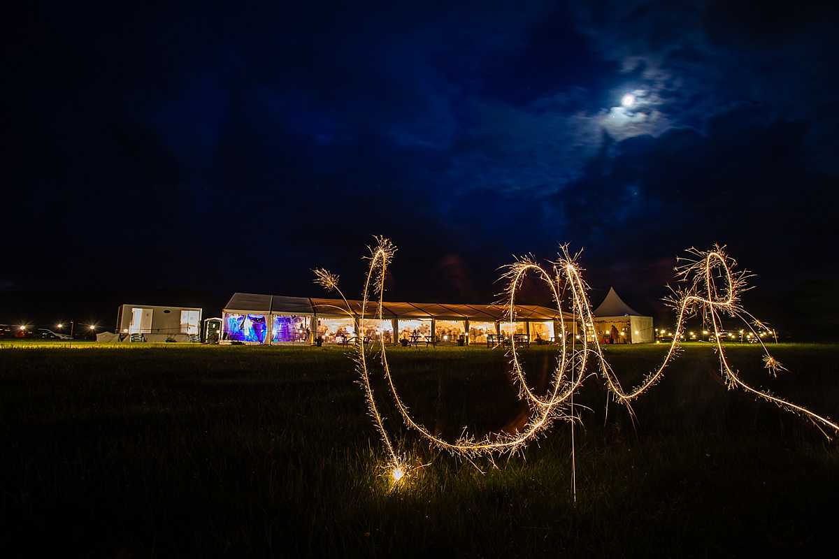 love written in sparklers with the marquee in the background for wedding in Machynlleth - charlotte giddings photography