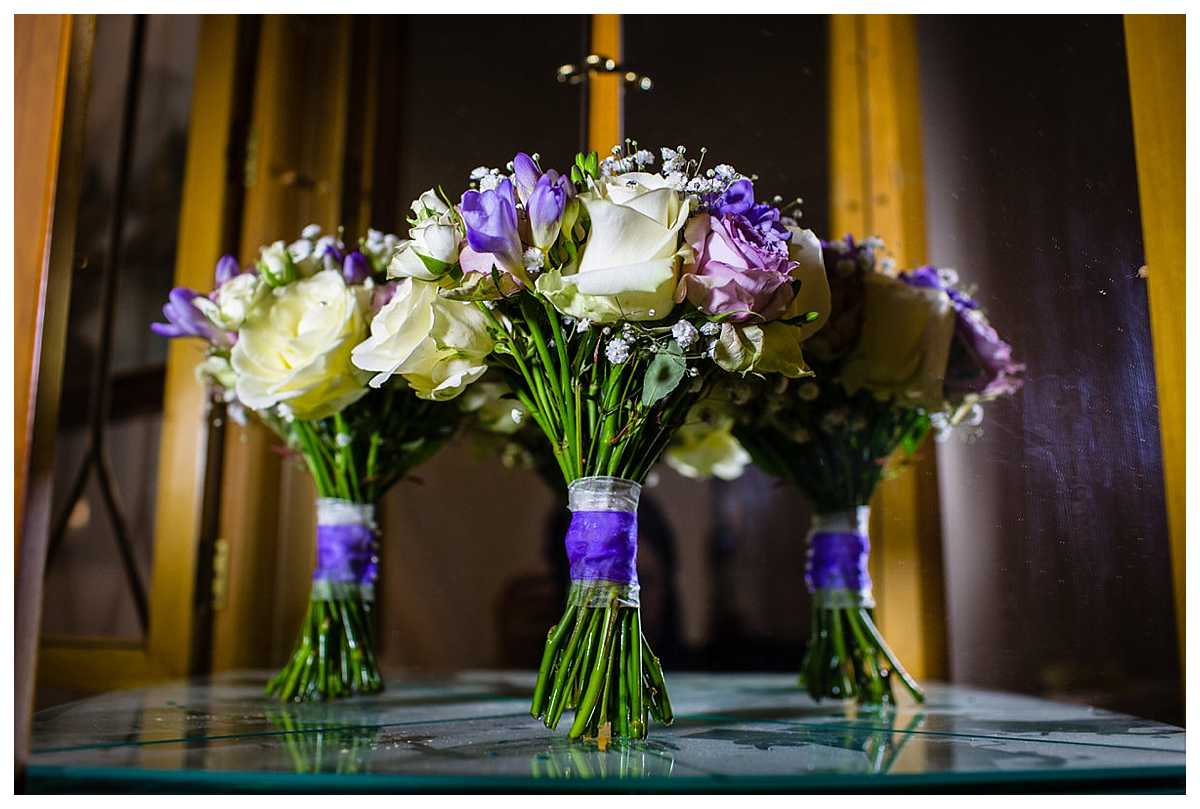 cream, pink and purple coloured inspired wedding bouquet sat in a cupboard surrounded my reflections
