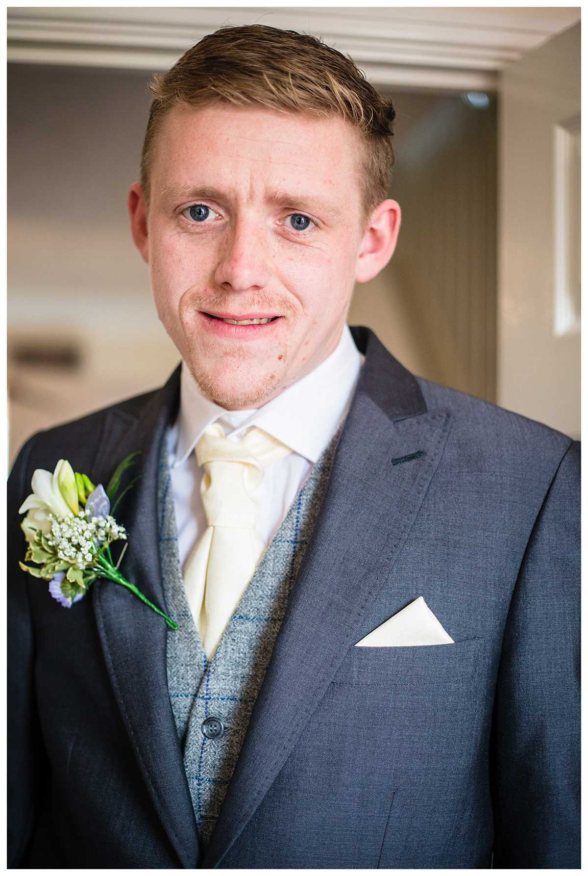 portrait of the groom wearing grey suit and pale yellow cravat and pocket square