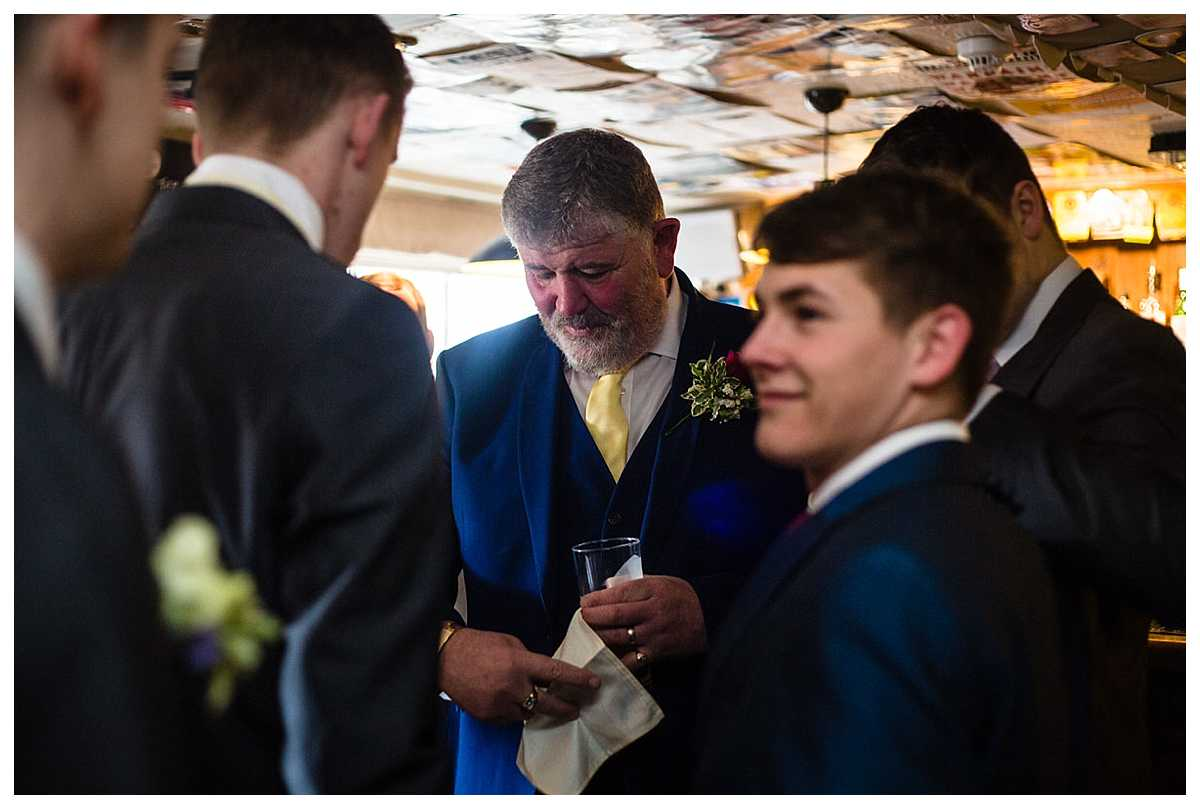 wedding guest helping the groom with his cream pocket square in the pub before they go to church