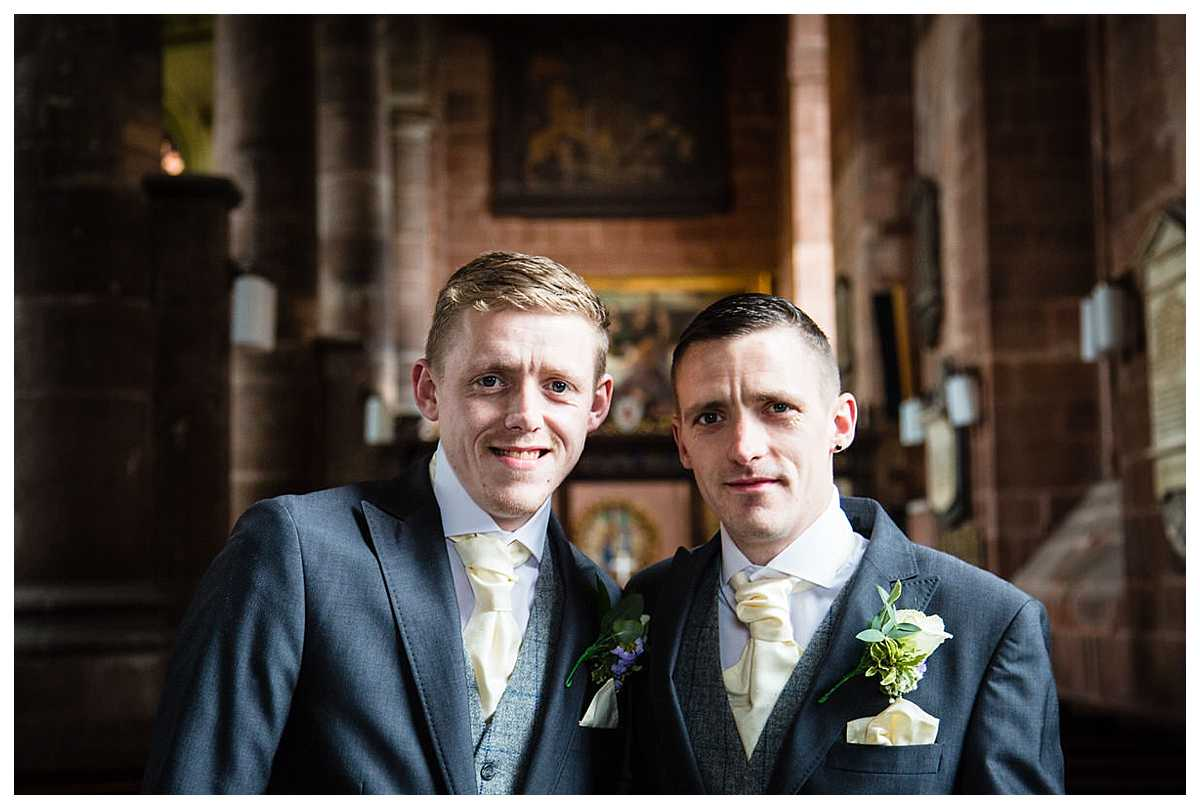 groom and the best man have a photo together in natural window light at whitchurch shropshire church