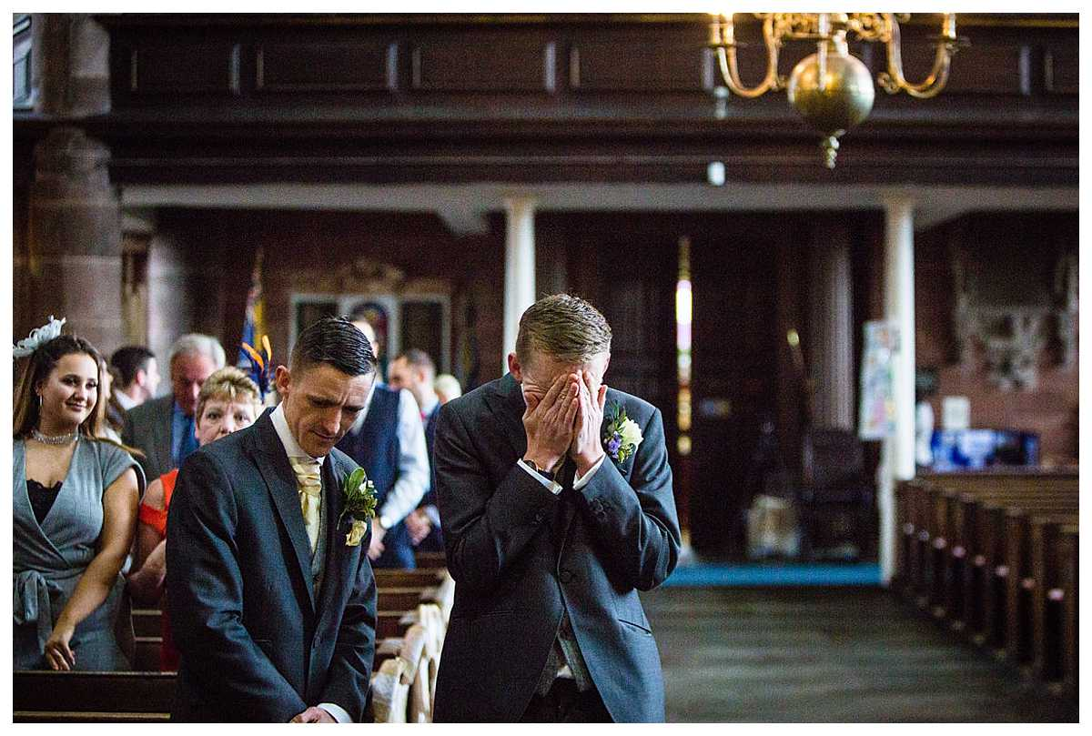 an emotional groom coving his face crying before his beautiful bride walks down the aisle at st alkmunds church, shropshire