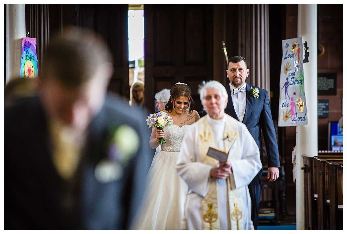 bride looking down as she walks down the aisle in st alkmunds church but looking very excited