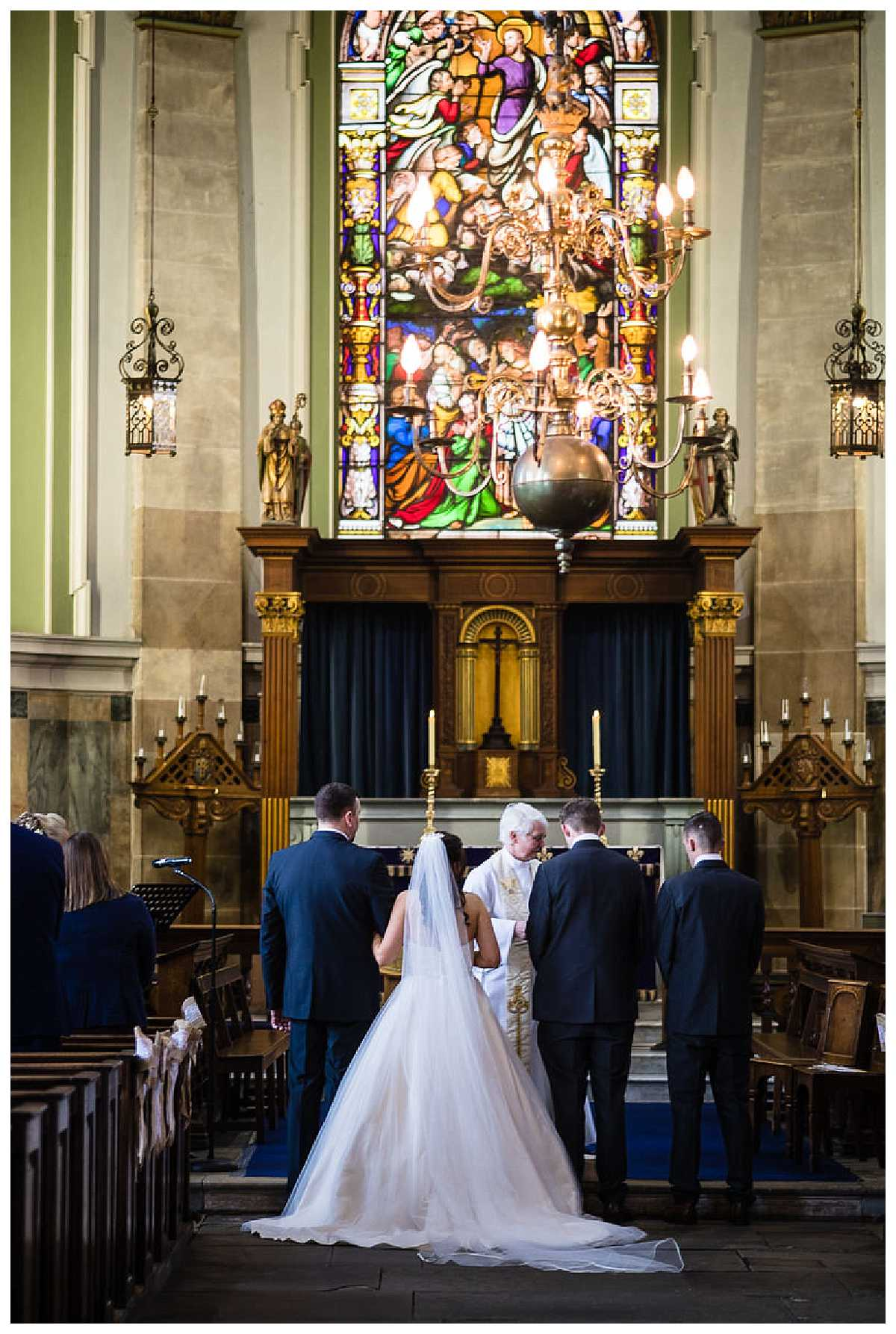 view from the back of the church with a large beautiful stainglass window and the bride, groom , father of the bride and the best man