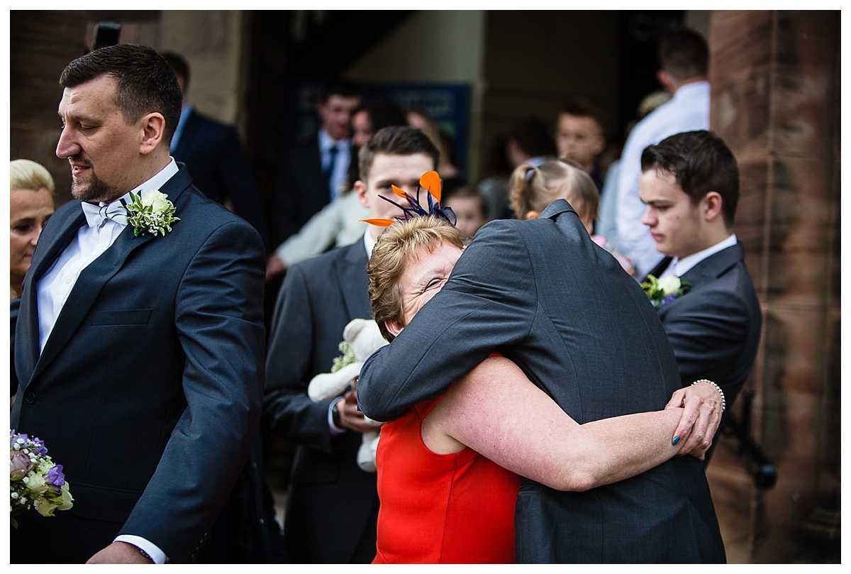 mother of the groom giving her son the biggest of cuddles outside church after the wedding ceremony