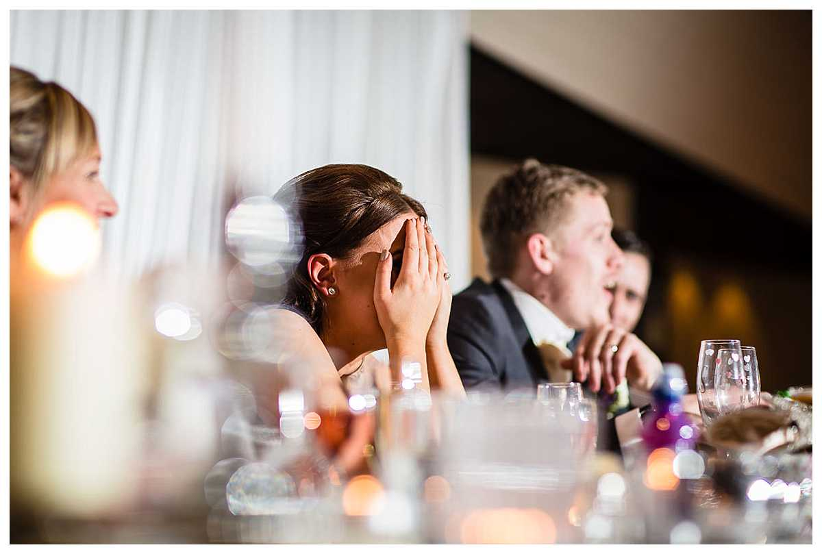 bride covering her face as she seems shocked and embarrassed during father of the bride speech