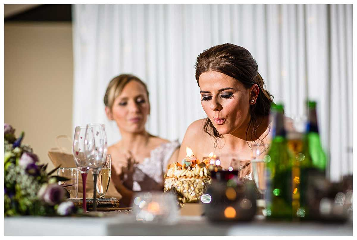 bride blowing out her candles on her birthday cake at her wedding reception