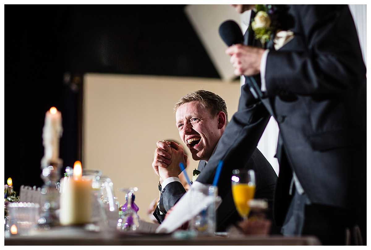 groom laughing out loud as his brother tells a funny tale during the best man speech
