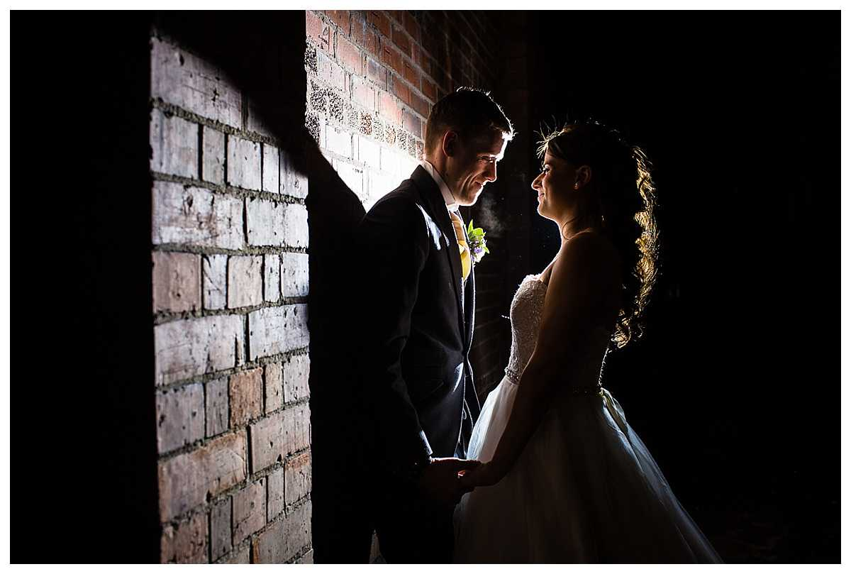 groom leaning against the wall and bride close for an artistic photo with flash lighting