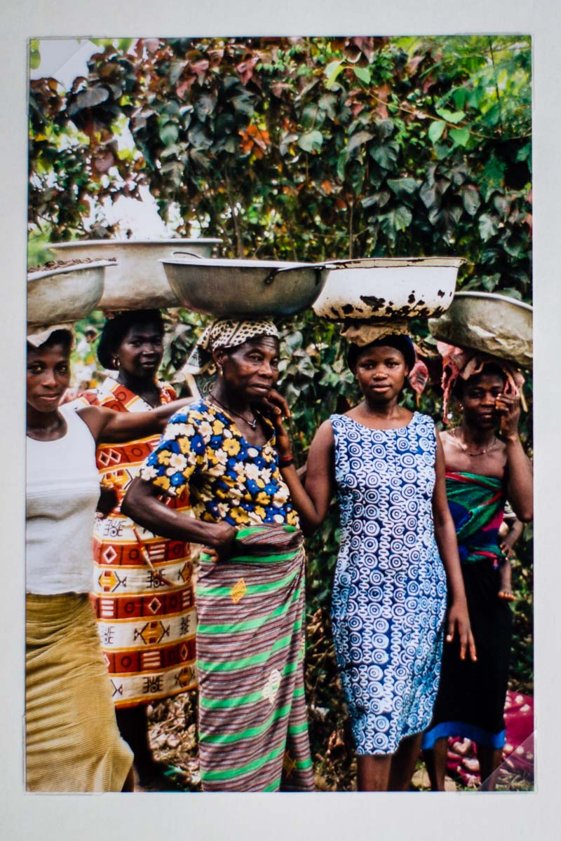 beautiful ghanian ladies standing together united as they hold bowls on their heads which they have used to carry soil and fill the floors in on the school projects
