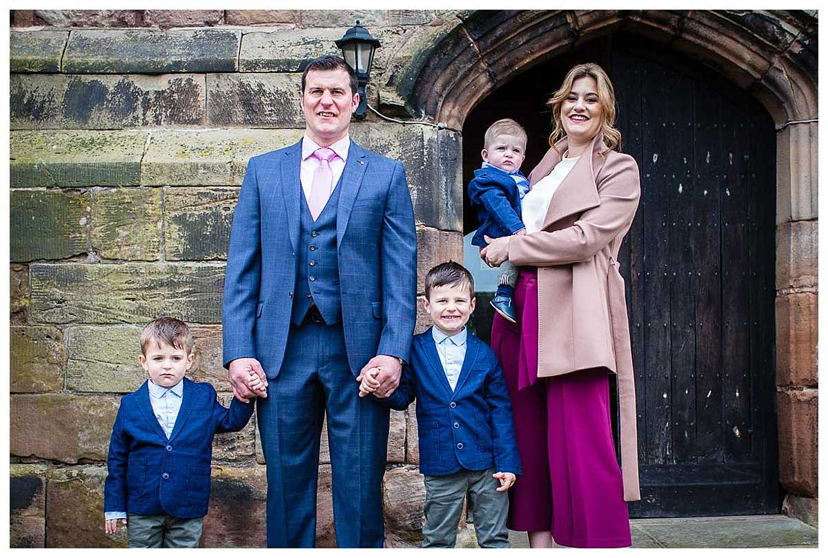 christening photographer taking a family photo of family three boys outside audlem church cheshire