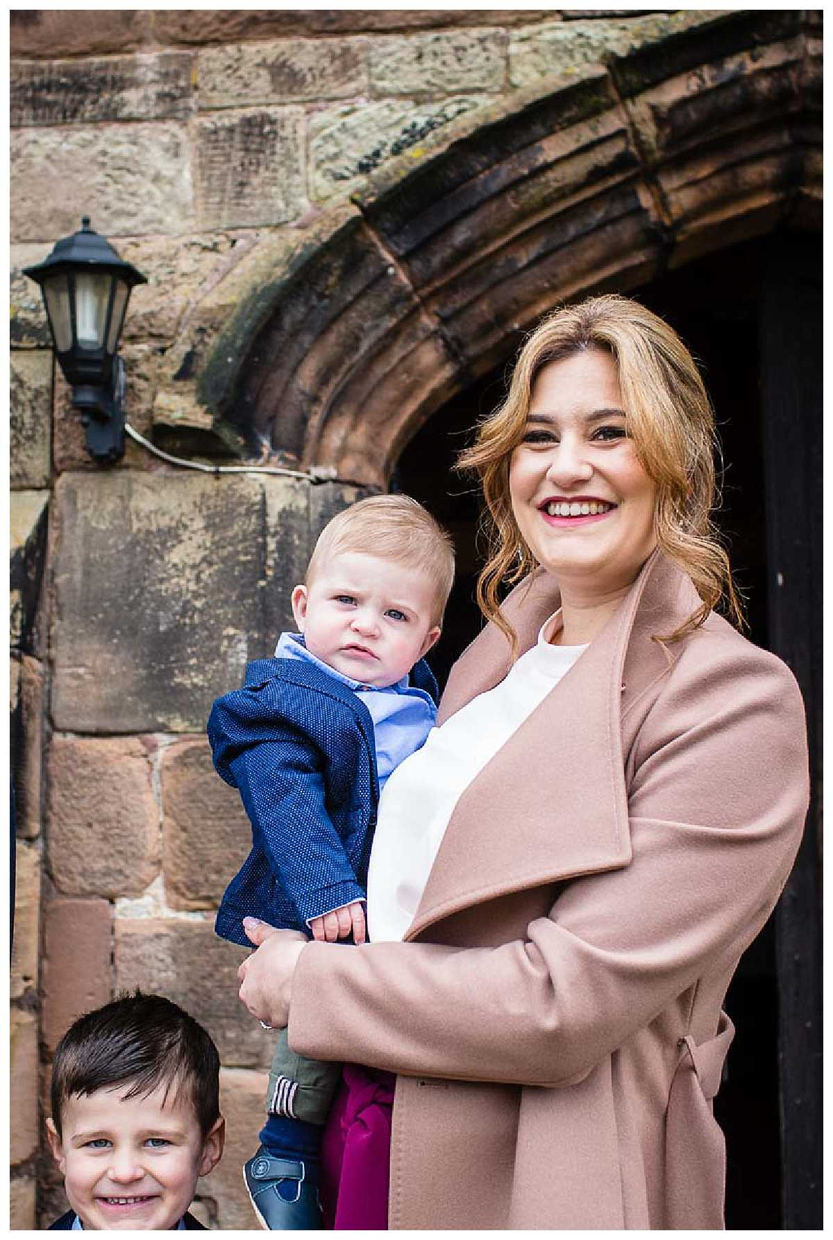 mum with beaming smile with baby boy for christening at st james church