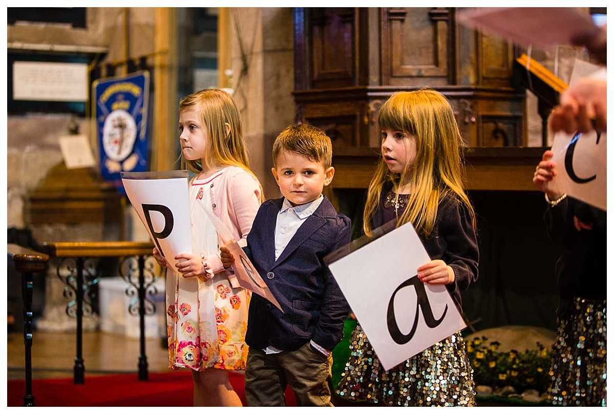little boy with his hand in his pocket looking rather cool as he helps the vicar in church, cheshire christening
