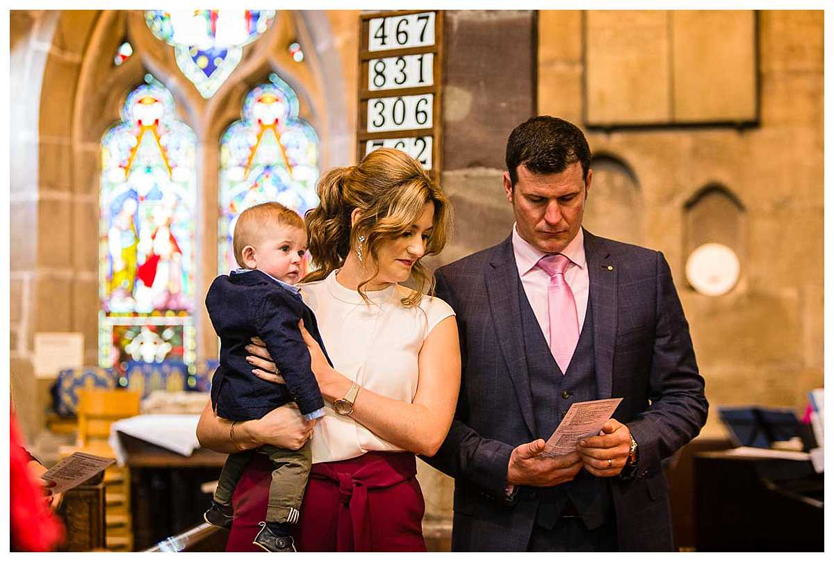 parents close together as they resight what is said for being a parent/godparents while holding the little boy who is being christened