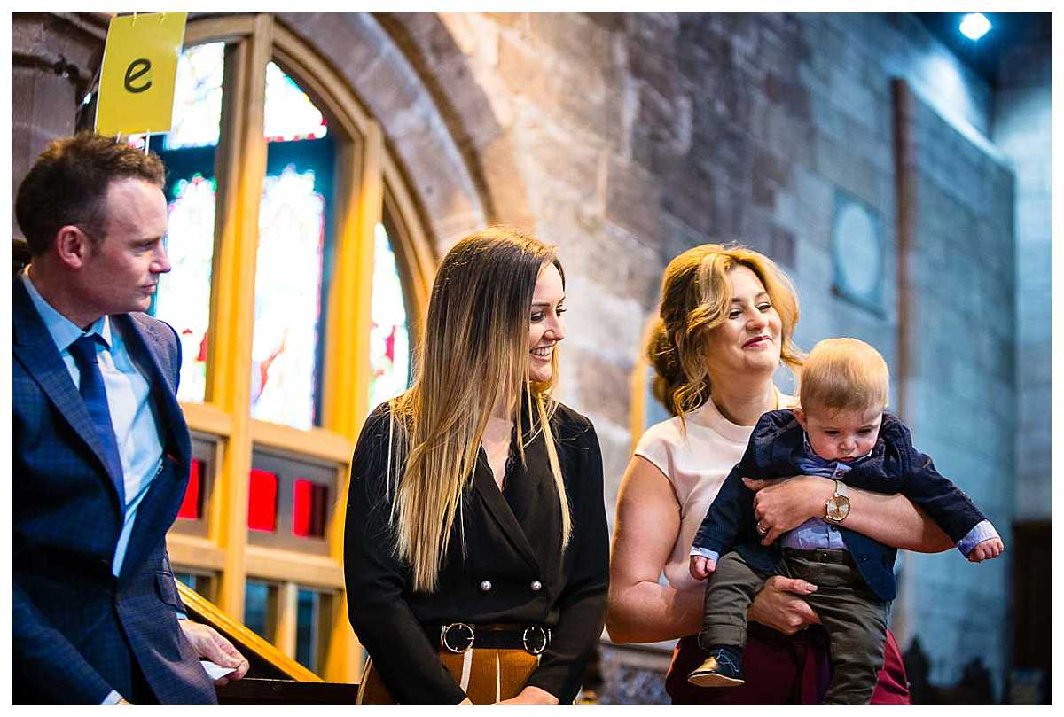 godmother smiling sweetly at little boy who is about to baptised by the vicar
