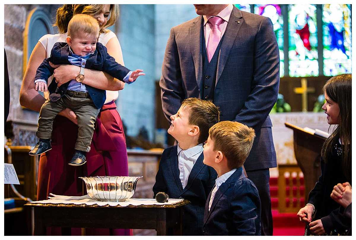 three brothers waving and laughing at each other before the youngest is christened - capture by christening photographer