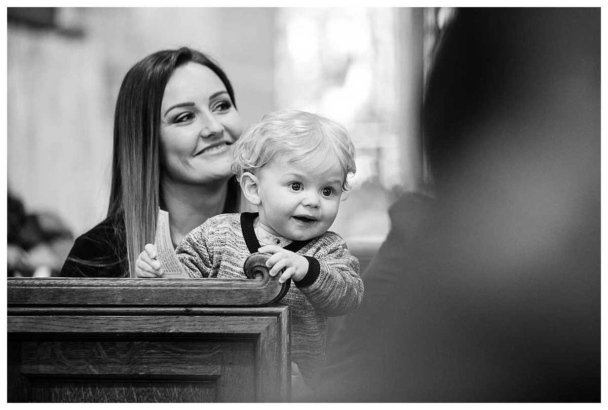 baby boy holding on the seat end as mum is smiling - st james's church, audlem, cheshire