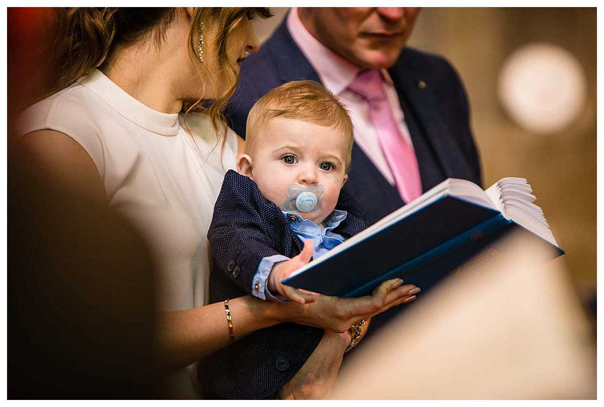 baby with big blue eyes as he is with mum and dad as they sing during the christening service