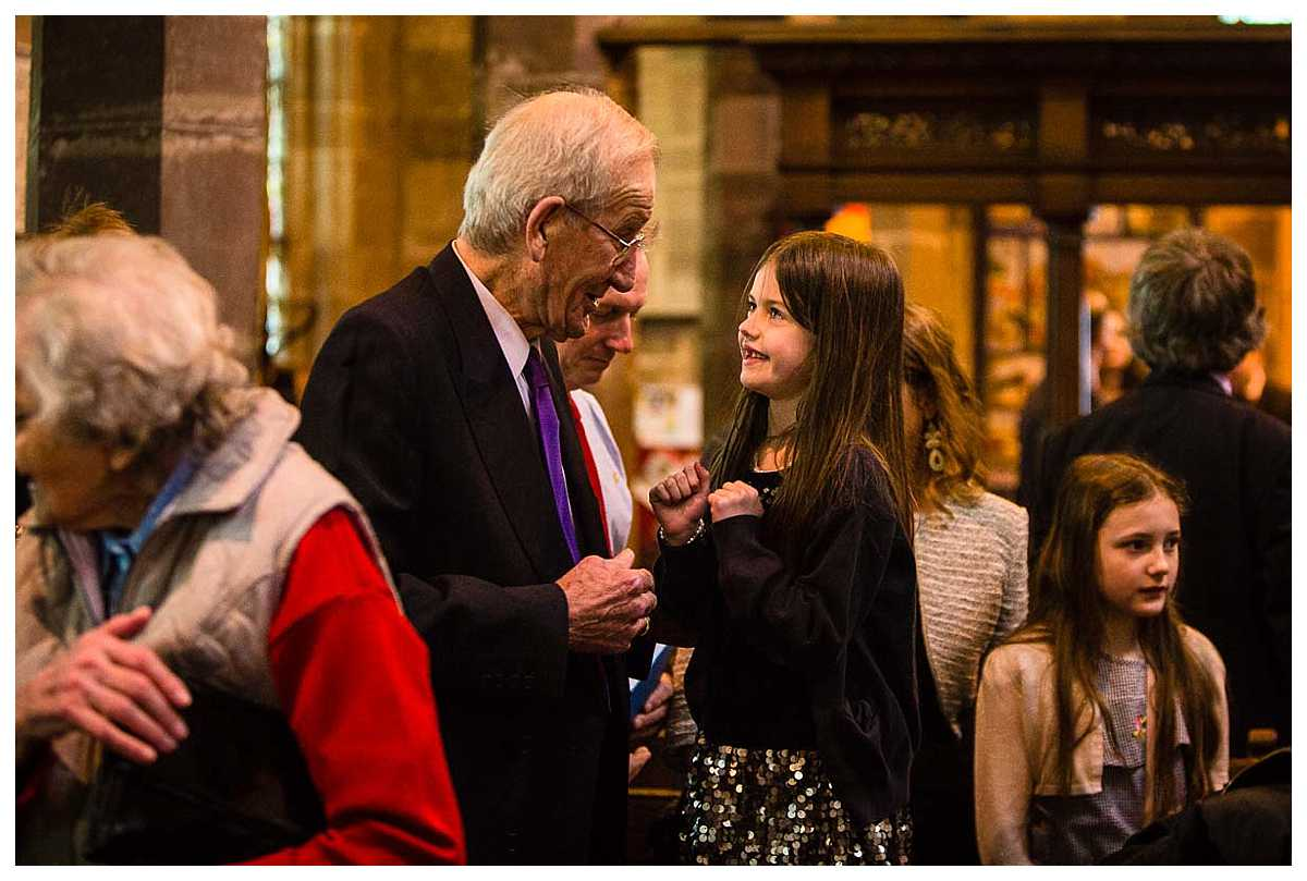 little girl and grandad playing around at the end of the christening service