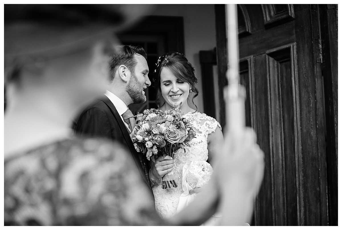 bride and groom nice and close under umbrella at wedding in wales