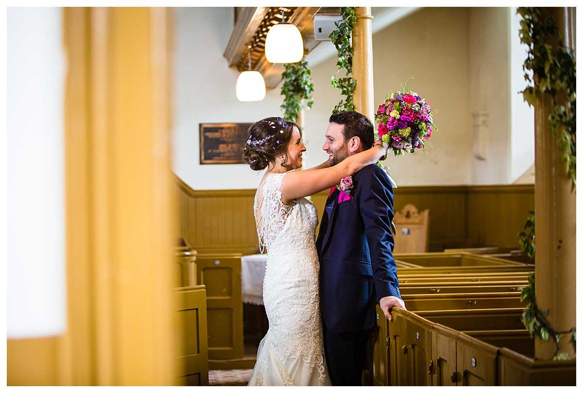 bride and groom giggling between themselves as they have portraits in church as there is rain on our wedding day
