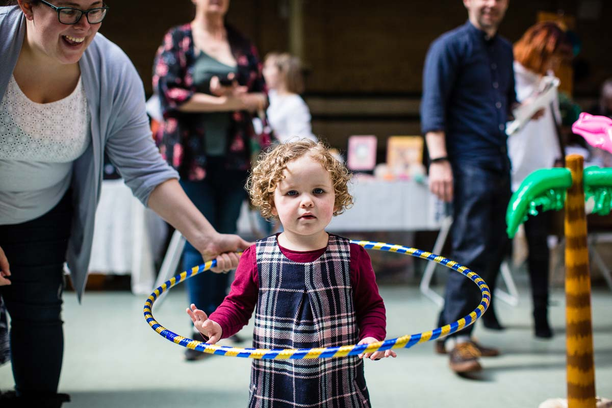 little girl playing with her mum and large hula hoop on the dance floor manchester parentfolk event