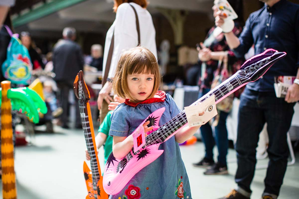 little girl with a cool bob hair cut giving it attitude playing a pink blow up guitar captured by victoria baths manchester photographer