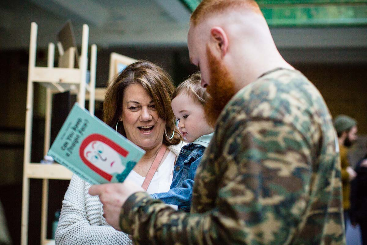 mum and dad reading books with little boy at the manchester family event