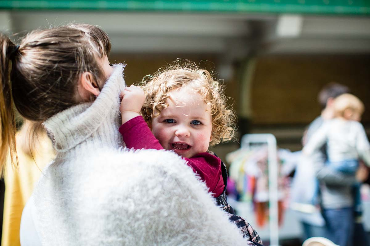 little girl with beautiful curly hair playing hide and seek with her mum victoria baths manchester photographer